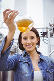 Woman looking at camera while holding beaker of beer