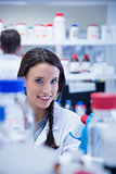 Smiling chemist picking up the bottles on the shelf