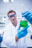 Chemist holding up beaker of green chemical