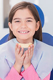 Smiling young patient holding teeth