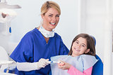 Smiling dentist teaching to her young patient how use toothbrush