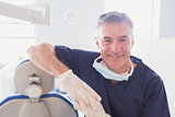 Smiling dentist leaning against dentists chair