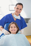 Pediatric dentist putting on her young patient the scrubs