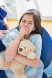 Scared patient covering mouth and holding teddy bear