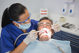 Dentist examining a patient with tools and light