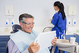 Smiling patient holding a mirror