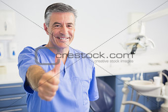 Portrait of happy dentist with thumbs up