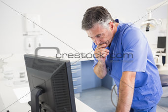 Thoughtful dentist using computer