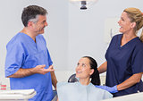 Smiling dentist and nurse speaking with their patient