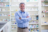Portrait of a smiling pharmacist standing with arms crossed