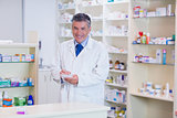 Portrait of a smiling pharmacist writing down notes