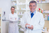Pharmacist and his trainee with arms crossed behind