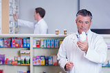 Concentrating pharmacist reading label on medicine jar