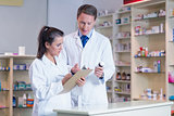 Trainee holding a prescription while talking to the pharmacist