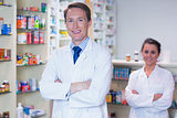 Pharmacist with his trainee standing with arms crossed