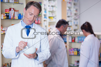 Focused pharmacist using mortar and pestle
