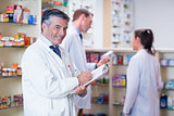 Smiling pharmacist in lab coat writing a prescription