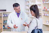 Customer handing a prescription to a pharmacist