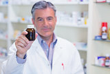 Pharmacist showing a drug bottle to camera