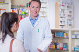Smiling pharmacist holding a paper bag looking at camera
