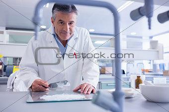 Smiling biochemist preparing some medicine