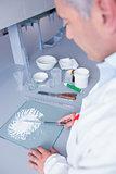 Biochemist standing while preparing some medicine