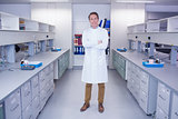 Portrait of a smiling biochemist standing with arms crossed