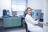 Smiling young biochemist using laptop at her desk