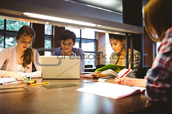 Thoughtful students working together at desk using laptop