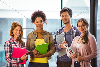 Four smiling classmates standing in front of the window