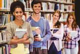 Happy students holding books in row