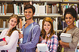Students in a line smiling at camera holding books
