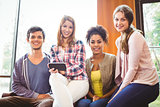 Happy students sitting on a sofa using mobile phone
