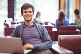 Happy young student sitting on couch using laptop