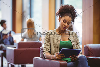Focused student sitting on sofa using her tablet pc