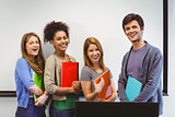 Students standing and smiling at camera holding notepads