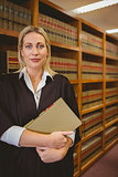 Serious lawyer holding a file while standing