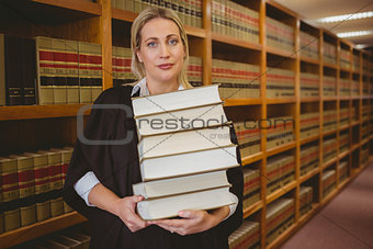 Lawyer holding heavy pile of books standing