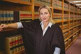 Smiling lawyer leaning on shelf