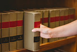 Hand taking a book from bookshelf