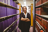 Unsmiling lawyer standing between shelfs with arms crossed