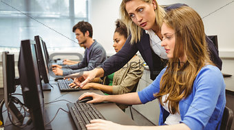 Attractive teacher helping her student in computer class