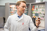 Handsome pharmacist looking at medicine