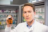 Handsome pharmacist holding medicine jar