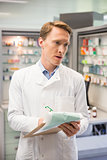 Focused pharmacist writing on clipboard