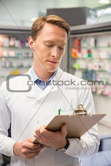 Focused pharmacist writing on clipboard