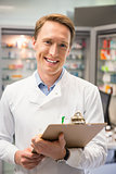 Happy pharmacist writing on clipboard