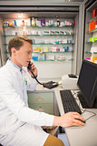 Serious pharmacist on the phone using computer