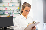 Junior pharmacist writing on clipboard