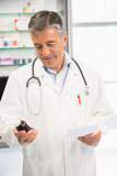 Happy pharmacist holding medicine jar